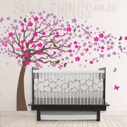 The Blowing Cherry Tree Wall Art is a giant tree with hundreds of cherry blossoms on the tree and blowing around the room
